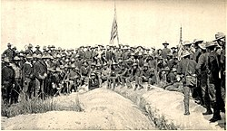 A black and white photo of US Army soldiers on 3 3 July 1898, in an upside down V type formation on top of Kettle Hill; two American flags are center and right. Soldiers facing camera.