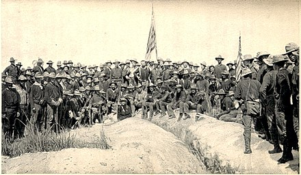 A black-and-white photo of US Army soldiers on July 3, 1898, in an upside-down V-type formation on top of Kettle Hill, two American flags in center and right. Soldiers facing camera.