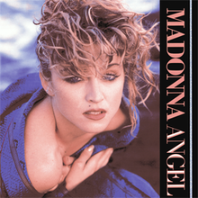 "Top view of a blond with rough, scrambled hair. She wraps a blue cloth around herself with her hands closing it on her chest. On the right hand side of the image, the words ""Madonna"" and ""Angel"" are written from top to bottom in capital peach letters."