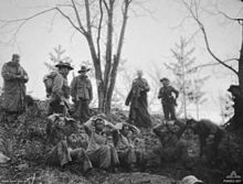 Five Asian soldiers sitting on a hillside with their hands behind their heads, while above them stands a group of Caucasian soldiers wearing slouch hats