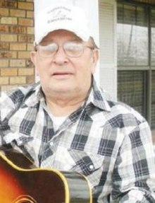 Photo of the upper body of a man who is wearing a hat and is holding a guitar