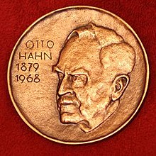 A medallion with an embossed image of Otto Hah.n