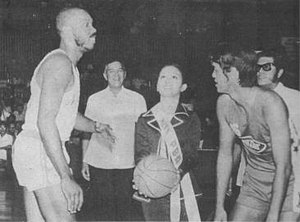 Basketball in the Philippines - Ms. PBA, Mia Montemayor tosses the ceremonial ball between Mariwasa's Cisco Oliver and Concepcion's Ramon Lucindo during the opening ceremonies of the Philippine Basketball Association on April 9, 1975. Looking on are PBA commissioner Leo Prieto and PBA president Emerson Coseteng.