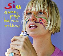 "Sia stands against a light blue background holding marker pens in front of her face. There are drawings on her face. To the left of her, the name ""Sia"" and the title ""Some People Have Real Problems"" is stylised in a colourful handwritten font."
