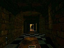 A long, darkened stone hallway with a light at the far end, against which a figure is silhouetted. Carpet is placed down the middle of the black-and-white tiled floor, and a black object protrudes from the bottom right corner of the image.