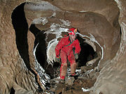 Caver in an Alabama cave showing common caving wear: overalls and helmet-mounted lights.