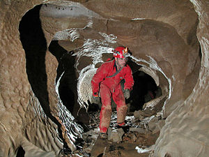 Caving - Caver in an Alabama cave showing common caving wear: coveralls, helmet-mounted lights, heavy boots and gloves.
