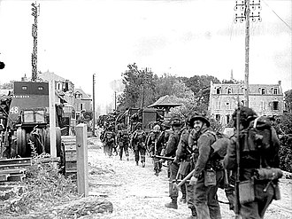 3rd Canadian Division - Tanks and Régiment de la Chaudière moving along French village road, Normandy Beach head