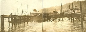Puget Sound mosquito fleet - King & Winge shipyard, in West Seattle, looking south, circa 1915 (but possibly earlier): The sternwheeler Vashon is on the marine railway at right.  The lookout tower of the original clubhouse of the Seattle Yacht Club, originally just south of the shipyard, can also be seen.