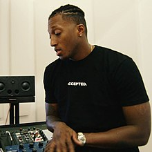 Lecrae sitting in a recording studio.jpg