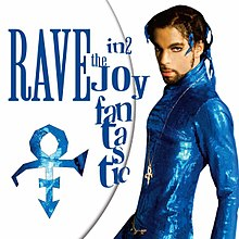 Prince wearing a blue, skin-tight outfit stands in front of a white background, staring into the camera.