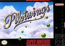 "The image shows a cursive title ""Pilotwings"" in front of a cumulus cloud-covered sky and a ring made of green orbs visible on the bottom right. The artwork has a black border with various labels on it."