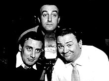 Peter Sellers, Spike Milligan kaj Harry Secombe pozas ĉirkaŭ BBC-mikrofono