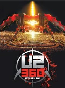 A tour stage; four large legs curve up above the stage and hold a circular video screen above the band. The legs are lit up in red and a spire that runs through the center of the stage illuminates the audience with yellow light. A grey circle is drawn below the photograph with the words U2 360° at the Rose Bowl written in the center; 360° is written in red, and the rest is written in grey. Two claws extend downwards in either side, representing a stylized drawing of the stage.