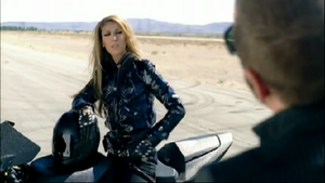 Taking Chances (song) - Celine Dion in the music video, where she is on a motorcycle, staring at David A. Stewart, after doing dangerous things.