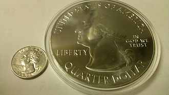 America the Beautiful Silver Bullion Coins - A normal sized quarter (left) sitting next to a bullion coin in a plastic holder (right).