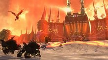 Screenshot showing a giant concert stage dominating the background, accented by gothic elements such as towering spires; the foreground shows several forces converging on the stage, including a flying winged creature, two people mounted on bear-like creatures, a giant brute, and several other ground forces.