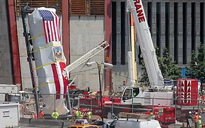 New York City Fire Department Ladder Company 3 - Sheathed in plastic and US and FDNY flags, workers prepare to lower Ladder 3's apparatus into the National September 11 Memorial & Museum.