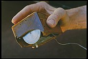 The first computer mouse, held by inventor Douglas Engelbart, showing the wheels that make contact with the working surface