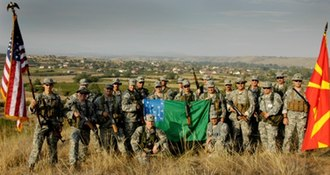 Vermont National Guard - Vermont National Guard members supporting Operation Rising Phalanx stand with U.S. and Macedonian troops holding the Green Mountain Boys battle flag in the Republic of Macedonia.