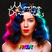 "A brunette woman is standing against a black background, with pink and blue neon lighting shining against her hair. Above her, the name ""Marina and the Diamonds"" is placed, while below her is the title ""Froot"" in colourful lettering."