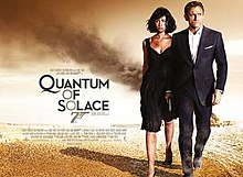 "A man in a business suit holding a gun with a woman in a black dress walking away from a destroyed facility in the desert. To their left is the title ""Quantum Of Solace"" in black letters – except the 'O's, which are golden and make a diagonal straight line with a 7 resembling a gun."