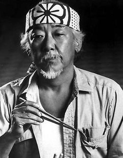 "Black and white photo of Mr. Miyagi (from the movie, ""The Karate Kid) holding chopsticks and looking calm and wise."
