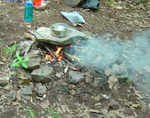 Cooking in the outdoors using a heated stone