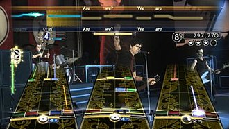 """Green Day: Rock Band - Green Day: Rock Band features gameplay similar to other games in the Rock Band series, played by avatars of the Green Day band members at recreations of venues from their concert tours. This screenshot shows """"Are We the Waiting/St. Jimmy""""."""