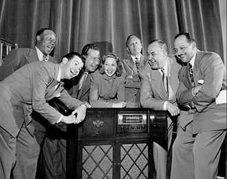 "Mel Blanc - The cast of The Jack Benny Program, from left to right: Eddie ""Rochester"" Anderson, Dennis Day, Phil Harris, Mary Livingstone, Jack Benny, Don Wilson, and Mel Blanc"