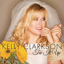 "Clarkson in a wedding dress had her left hand tied up to her groom, whom she looks on, smiling, while holding a sunflower bouquet on her right hand. The words ""Kelly Clarkson"" and ""Tie It Up"" were written in the lower middle in black letters."