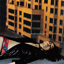 Madonna laying down at the corner of a rooftop, with yellow buildings present behind her. She wears a black shining jacket.