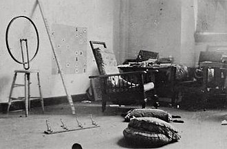 Readymades of Marcel Duchamp - Marcel Duchamp's studio at 33 West 67th Street, New York City, 1917–18. Shown to the left is the 2nd version of Bicycle Wheel, 1916-17. The original 1913 version and this 2nd version are lost. The coatrack, titled Trap (Trébuchet), 1917, is on the floor, lower left.