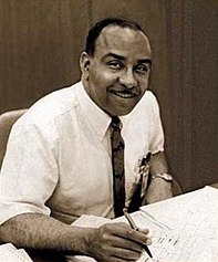 portrait seated at his desk in shirtsleeves and tie with pen in his hand