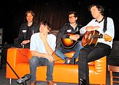 Four men sitting on an orange sofa, two holding guitars and one behind keyboards that are set on the left arm of the sofa.
