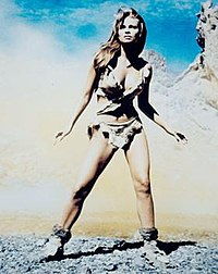 Welch in fur bikini, in smoky, rocky surroundings, stands with feet braced apart, hands away from sides, tensed as if seeing a threat in the distance.