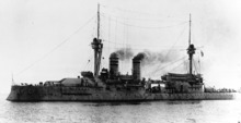 A large ship steaming, black smoke belching from her funnels, with many crewmen on the decks