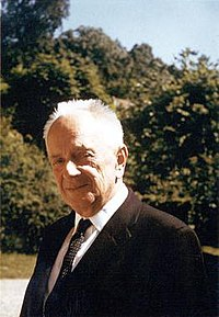 Outdoor photograph of an older man with thinning white hair, dressed in a suit.