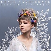 Head and shoulders of Grace VanderWaal, a teenage girl, gazing to her right. She has flowers in her hair, which are piled on her head.