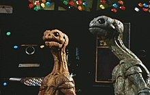 Two reptile-like alien creatures, one blue and one orange, look in an upward direction, with machinery and computer screens in the background.
