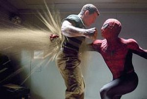 Spider-Man 3 -  alt=Spider-Man punches Sandman, and his fist is seen on the other side of his chest, with sand blowing through the hole