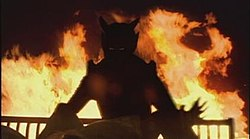 Silhouette of a demon, with fire in the background.