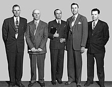 Five men wearing suites stand side by side