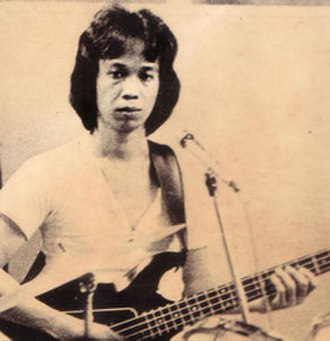 Chrisye - Chrisye playing the bass in 1977. He sported long hair for most of his career, until his chemotherapy in 2005.