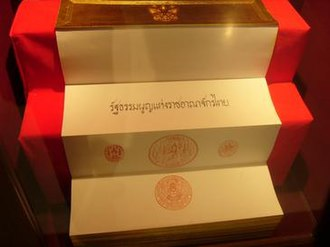2007 constitution of Thailand - The original copy of the 2007 constitution, written on a traditional folding book (samut thai). On the pages shown, King Bhumibol Adulyadej signed and applied his regnal seal (the seal of the garuda) and the three great seals (from left to right: the seal of the great mandate, the seal of the celestial elephant, and the seal of the phoenix castle). The copy is displayed at the National Assembly of Thailand along with the copies of the other constitutions.