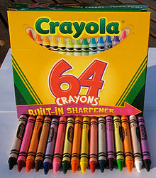 Crayola yellow and green 64-color box with 16 of the crayons from the box arrayed in front of it