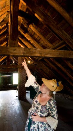 Jacques Guibourd Historic House -  Docent pointing out the Norman truss (king post) roof system