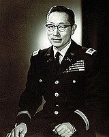 Korean American male wearing a United States Army Dress Blue uniform and eyeglasses