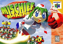 A female robot made of white, 3D spherical polygons is blasting towards the right side of the box art, with fist outstretched and a trail of fire behind her. On the ground is a legion of identical, sad-faced creatures. The logo is in big, green bubble letters, and the Nintendo 64 sidebar flanks on the right.