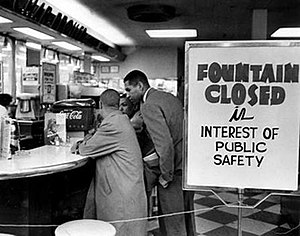 "Lunch counter with four young black men seated at bar stools along the counter. They are not being served and are simply sitting. A sign on the checkerboard-tiled floor reads ""Fountain closed in interest of public safety""."
